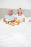 Portrait of mature couple having breakfast in bed Stock Photo