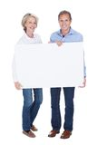 Portrait of mature couple holding placard Stock Images