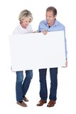 Portrait of mature couple holding placard Stock Photo