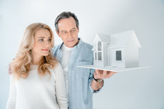 Portrait of mature couple looking at house model royalty free stock photos