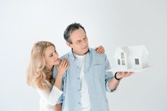 Portrait of mature couple looking at house model stock photo