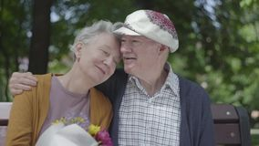 Portrait of a mature couple in love sitting on a bench in the park. Adult woman holds a beautiful bouquet of flowers stock video