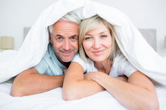Portrait of a mature couple lying in bed Stock Photo
