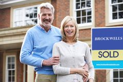 Portrait Of Mature Couple Outside New Home Standing By Sold Sign. Mature Couple Outside New Home Standing By Sold Sign Royalty Free Stock Image