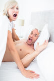 Portrait of mature couple shouting in bed Royalty Free Stock Photography