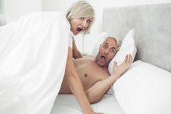 Portrait of mature couple shouting in bed Stock Images