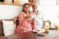 Portrait Of Mature Couple Sitting At Breakfast Table Stock Images