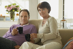 Portrait of a mature couple sitting on a couch and holding cups of coffee.  royalty free stock images
