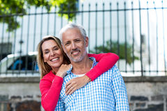 Portrait of mature couple standing against fence Royalty Free Stock Photo