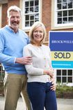 Portrait Of Mature Couple Standing Outside Dream Home Wit Sold Sign. Mature Couple Standing Oute Dream Home Wit Sold Sign royalty free stock photo