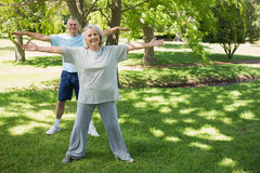 Portrait of mature couple stretching hands at park Royalty Free Stock Photos
