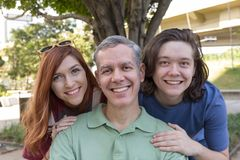 Portrait of Mature dad with children smiling. Concept of family, paternity, affection. Portrait of Mature dad with children smiling and looking at camera royalty free stock image
