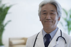 Portrait of mature doctor looking at camera and smiling Royalty Free Stock Photo