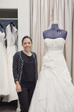 Portrait of a mature employee standing by elegant wedding dress in bridal store Stock Photos