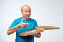 Portrait of mature european man eating a slice of pizza. In his hands he holds a box of food. Studio shoot. Concept of eating fast food at old age stock images