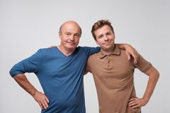 Portrait of mature father and son standing with serious expression on face. Good relatios in family. royalty free stock photo