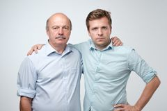 Portrait of mature father and son standing with serious expression on face. Good relatios in family. stock photo