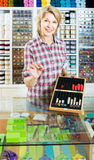 Portrait of mature female cashier at cash desk with many thimble Royalty Free Stock Images