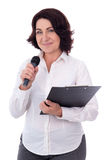 Portrait of mature female reporter with microphone and clipboard Stock Photo