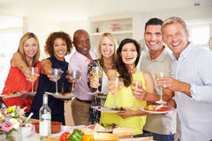 Portrait Of Mature Friends Enjoying Dinner Party At Home Stock Photography