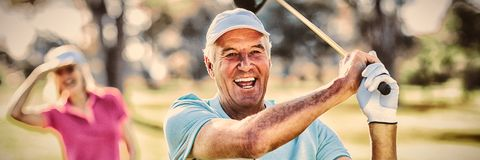 Portrait of mature golfer holding golf club stock photos