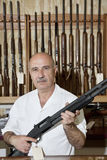 Portrait of a mature gun merchant with rifle Royalty Free Stock Photo