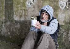 Portrait of a mature homeless man sitting outdoors holding out a tin. Close up portrait of a mature homeless man sitting outdoors holding out a tin Royalty Free Stock Photography