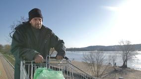Portrait of mature homeless man walking near river. Portrait of poor desparate mature homeless man walking near the river pushing shopping cart on a cold autumn stock video footage