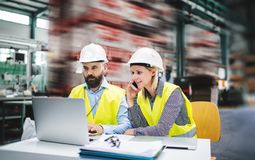 A portrait of an industrial man and woman engineer with laptop in a factory, working. A portrait of a mature industrial man and woman engineer with laptop and stock image