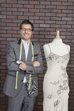 Portrait of mature male fashion designer standing next to tailor's dummy Royalty Free Stock Photo