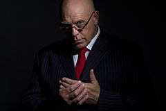 Portrait of mature male rubbing his hands together. Low key portrait of mature male in pin strip suit wearing glasses and rubbing his hands together. He can stock photos