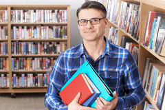 Portrait Of Mature Male Student Studying In Library. Mature Male Student Studying In Library Royalty Free Stock Image