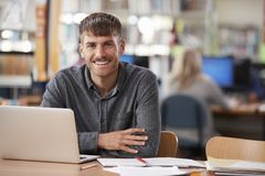 Portrait Of Mature Male Student Using Laptop In Library Stock Image