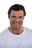 Portrait of mature man clenching teeth. Against white background Royalty Free Stock Photo