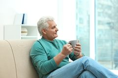 Portrait of mature man with cup of drink stock images