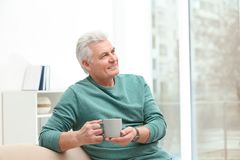 Portrait of mature man with cup of drink royalty free stock images