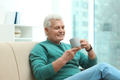 Portrait of mature man with cup of drink on sofa stock images