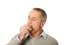 Portrait of mature man eating an apple.  stock image