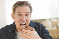Portrait Of Mature Man Having Donut At Home Royalty Free Stock Image