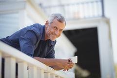 Portrait of mature man holding a coffee cup in balcony. At home Stock Images