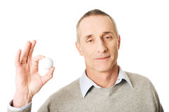 Portrait of mature man holding golf ball Royalty Free Stock Photo