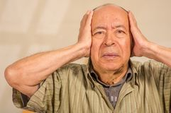 Portrait of a mature man holding his head with both hands, in a blurred background royalty free stock photos