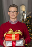 Portrait of mature man holding stack of Christmas presents Royalty Free Stock Photos