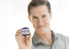 Portrait Of Mature Man Holding Vote Button Stock Photo
