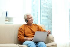 Portrait of mature man with laptop and headphones stock image