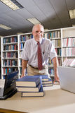 Portrait of mature man at library with textbooks. Portrait of mature man at library table with textbooks, professor researching royalty free stock photography