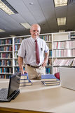 Portrait of mature man at library with textbooks Stock Image
