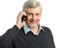 Portrait of mature man with phone. Close up of smiling elderly man speaking on mobile phone on white background stock image