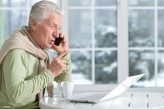 Man with phone using laptop. Portrait of mature man with phone using laptop Stock Photography
