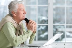 Portrait of man with phone using laptop. Portrait of mature man with phone using laptop Royalty Free Stock Photo